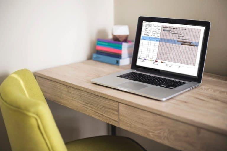 Dator på bord med en skärm som visar dokument med vit bakgrund och svart text