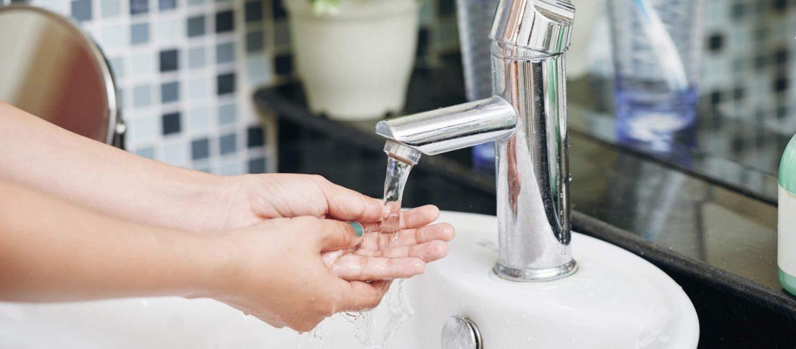 Händer som tvättas under vattenkran