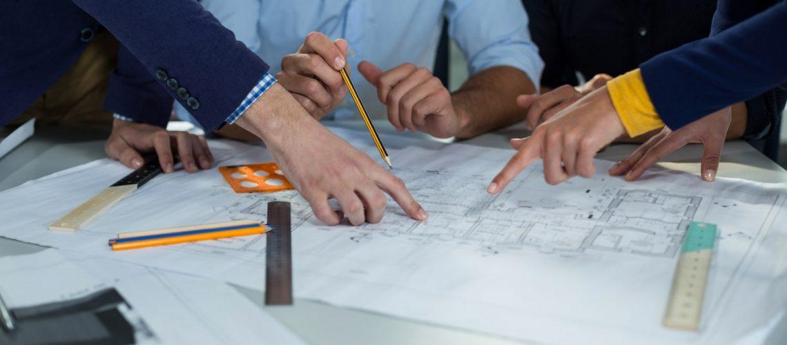 Möte där fyra personer planerar med hjälp av en planritning.
